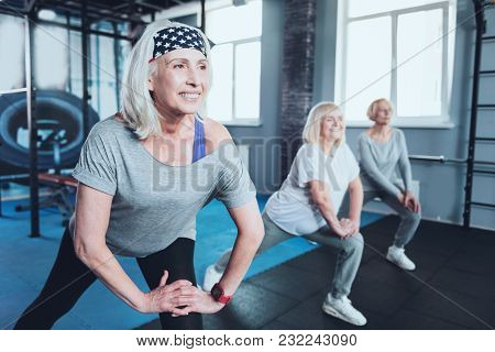 Say No To Arthritis Pain. Selective Focus On A Joyful Woman Smiling While Lunging With A Group Of El