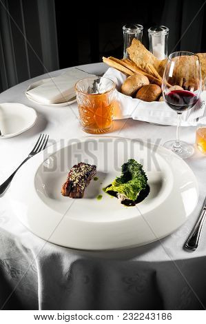 Main Dish With Meat, Red Wine And Crispy Fresh Bread On A Table With A White Tablecloth. Sharp Shado