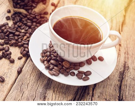Hot Coffee Cup With Coffee Bean On Wooden Table. Coffee Background For Cafe Or Coffee Shop