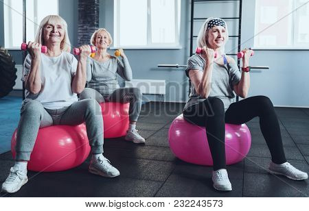 Say No To A Passive Lifestyle. Group Of Three Radiant Ladies Focusing On An Exercise While All Sitti
