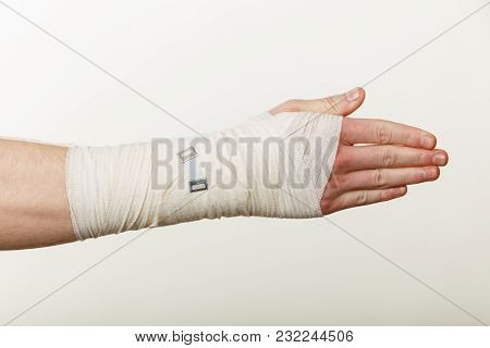 Fractures And Dislocations Concept. Male Hand In White Bandage. Helpful Medication For Painful Palm