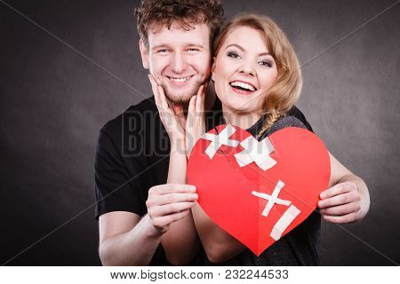 Heal Love Concept. Couple Woman And Man Holding Two Halves Of Broken Heart Fixed With Plaster Bandag