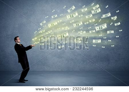 Caucasian male in business suit holding money,which flies through his hands