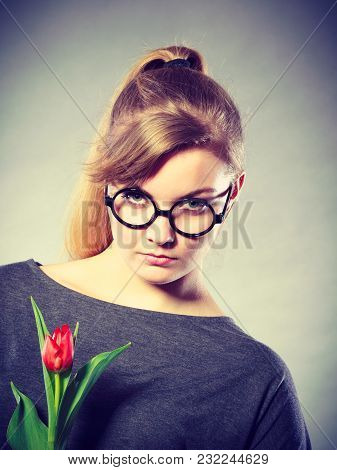 Disappointment And Stress. Young Upset Student Girl With One Single Red Tulip Flower On Gray Grey Ba