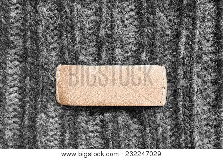 Blank Leather Clothes Label On Grey Knitted Background