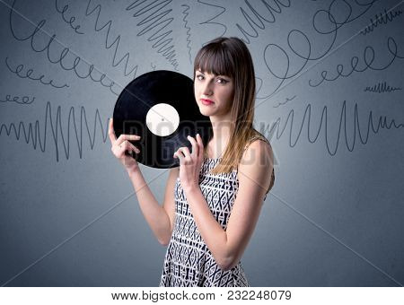 Young lady holding vinyl record on a grey background with scribbles around her