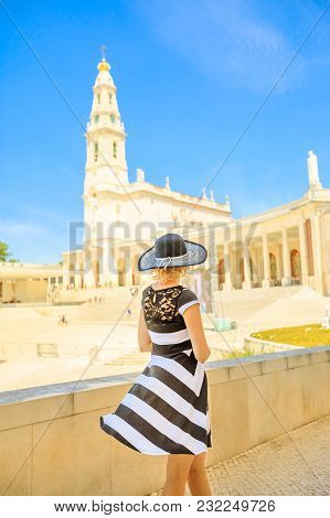 Religious Tourism In Portugal. Tourist Woman Walking At Basilica Of Our Lady Of Fatima, One Of Most