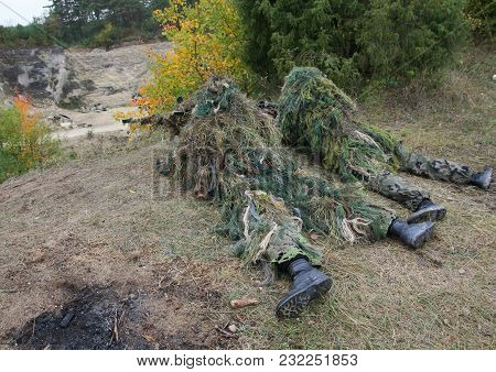 Two Camouflage Hunters Or Soldiers Hiding In Bushes In Camouflage Autumn Background. Sniper With Rif