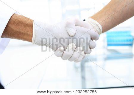 Handshake with white medical gloves