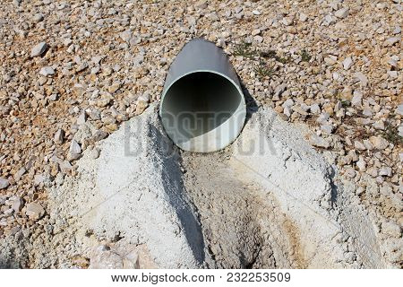Plastic Water Pipe Drain Surrounded With Gravel Small Dried Grass And Concrete On Sunny Winter Day