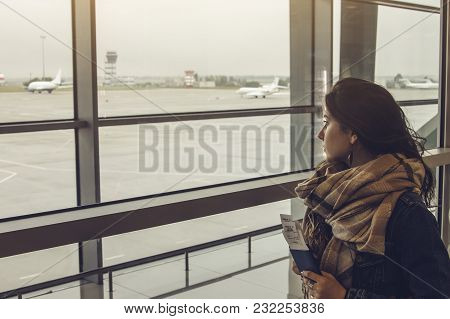 Young Woman Waiting For Her Flight At The Airport And Holding Tickets