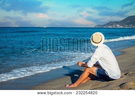 Young Man Having A Rest On The Beach In The Morning