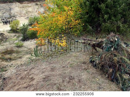 Camouflage Hunter Or Soldier Aiming Hiding In Bushes In Camouflage Autumn  Background. Sniper With R