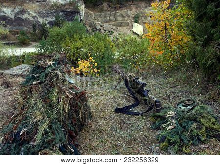 Camouflage Hunter Or Soldier Hiding In Bushes In Camouflage Autumn  Background. Sniper With Rifle.