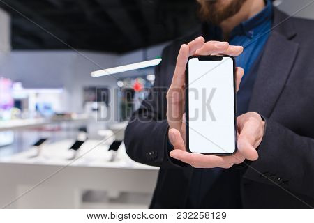 A Man In A Suit Holds In His Hands A Modern Smartphone With A White Screen. A Business Man Shows A T
