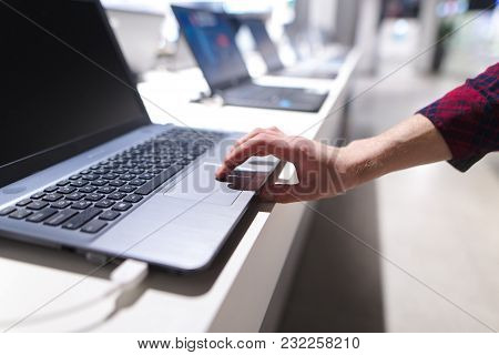 The Man Controls The Computer With A Touchpad. A Man's Hand Uses A Laptop In The Electronics Store.