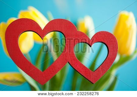 Two Red Hearts On Blurred Floral Background Of Yellow Tulips With Turquoise.