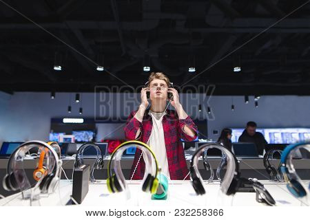 A Young Man Chooses A Headset In A Modern Store. Headphone Test. Portrait Of A Man In The Store Whil