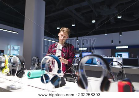 The Buyer Looks At The Headphones In The Electronics Store. A Young Man Chooses Goods To Buy In A Te