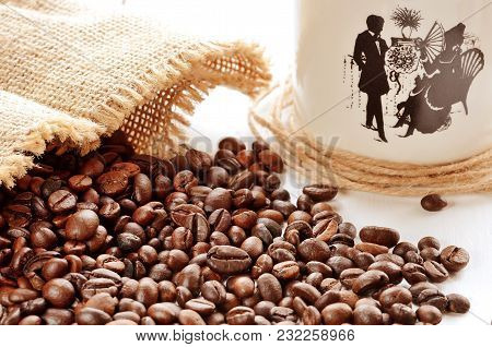 Close-up Of Spilled Coffee Beans From Canvas Sack And Porcellaneous Mug In Background