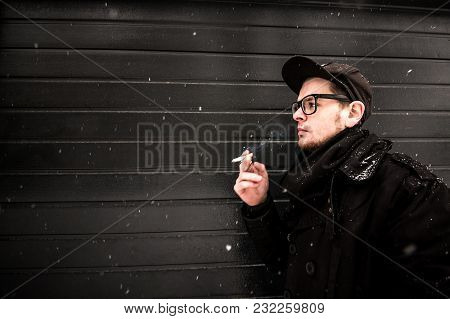 Smoking. A Young Man Smoking A Cigarette In Black Clothes On Black Texture Background With Snow