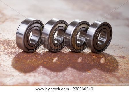Four Used Metal Bearings On Rusty Surface