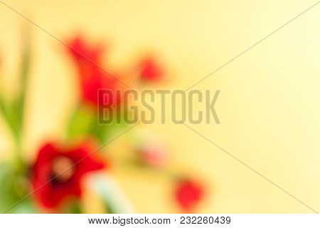 Abstract Floral Background With Blurred Spots Of Red Tulips On Yellow Background.