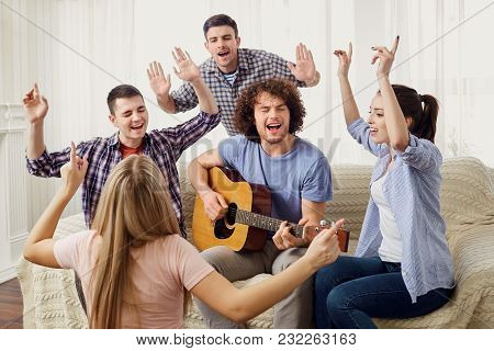 A Group Of Friends With A Guitar Sing Fun Songs At A Party Indoor.