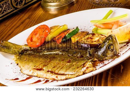 Whole Trout With Grilled Vegetables On White Plate
