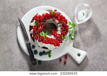 Bundt Cake With Fresh Berries And Sauce From Sour Cream On Grey Stone Table