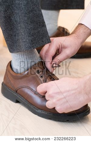 Close Up Of Adult Son Helping Senior Man Tie Shoelaces