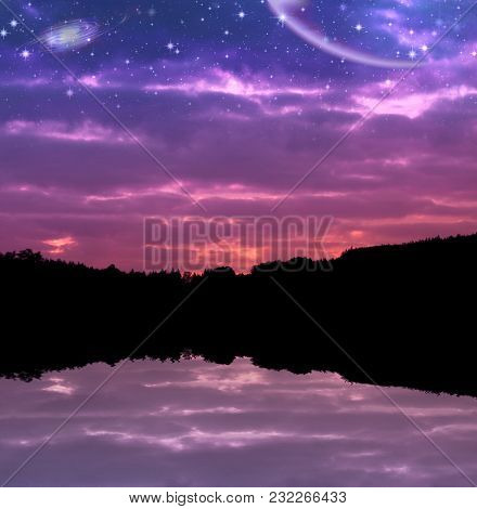 Magical Starry Sky With The Stars, Planets And Galaxies Over The Lake And Silhouetted Mountains With