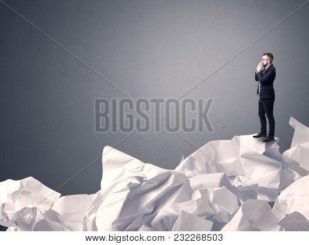 Thoughtful young businessman standing on a pile of crumpled paper with a grey background