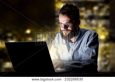 Young handsome businessman working late at night in the office with city lights in the background