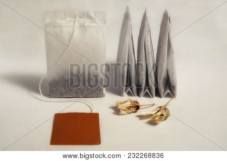 Tea Bags Of Black Tea Close-up On A White Background And Flowers Of Dried Chamomile And Free Space C