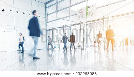 Crowd Of Blurred  People Walking At A Floor At A Fair. Ideal For Websites And Magazines Layouts