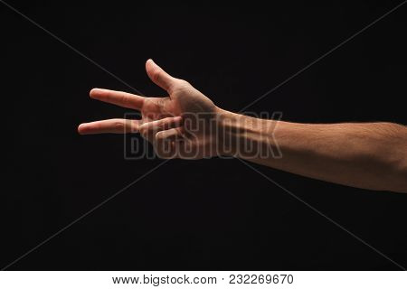 Male Hand Showing Three Fingers, Number Three Isolated At Black Background. Counting, Gesturing, Enu