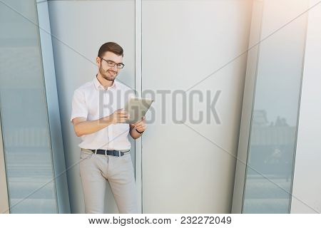 Attractive Smiling Businessman Or Lawyer In Eyeglasses Is Holding Digital Tablet While Standing Near