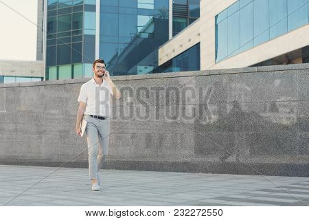 Smiling Businessman Is Talking On Cell Phone And Holding Digital Tablet In His Hand While Walking In