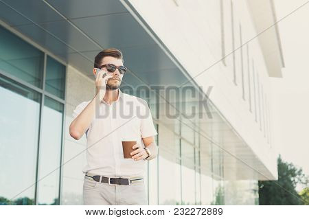 Young Pensive Businessman In Sunglasses Talking On Cell Phone, Looking Away And Drinking Coffee Whil
