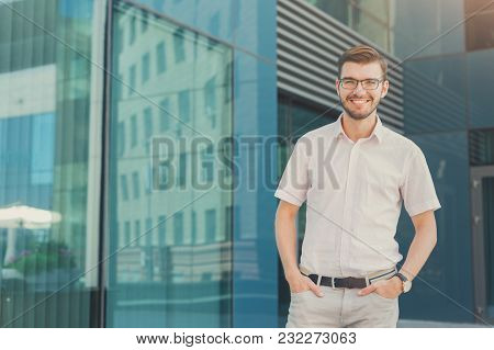 Portrait Of Happy Businessman Standing With Hands In Pockets Against Modern Office Building And Look