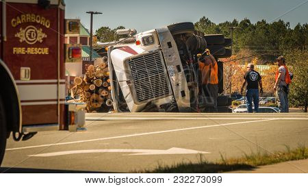 March 10, 2017: Carrboro Nc Usa-men Working On Overturned Logging Truck With Fire Truck Standing By