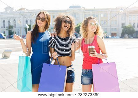 Happy Girls With Shopping Bags Outdoors. Smiling Female Friends In Bright Summer Clothes And Wearing