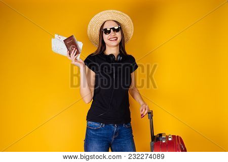 Happy Young Girl In A Hat And Sunglasses Goes On Vacation, Travel, Holds Plane Tickets And A Passpor