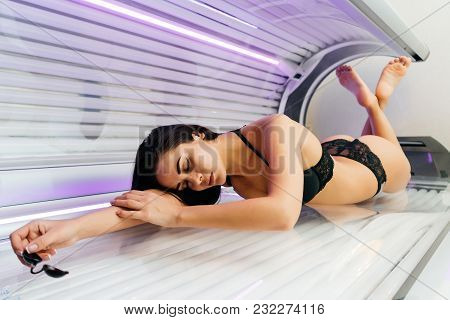 Beautiful Slender Young Girl In A Swimsuit Lies In A Horizontal Tanning Salon, Relax, Beautiful Tann