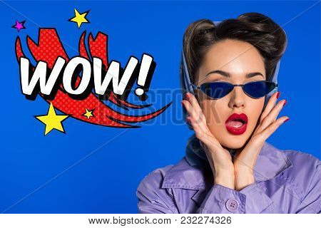 Portrait Of Stylish Woman In Retro Clothing And Sunglasses With Comic Style Wow Sign Isolated On Blu