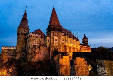 The Gothic Medieval Fortress Of Hunedoara In Romania, Shot In The Blue Hour