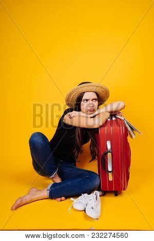 Sad Young Girl Is Going On A Trip, On Vacation, Sitting Next To A Large Suitcase