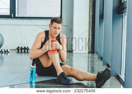 Sportsman With Injured Knee Resting On Mat In Gym