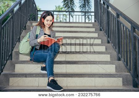 A Young Teenage Student In University Smiling And Reading The Book In Summer Holiday. She Listening